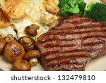 Sirloin steak with dauphinois potatoes, mushrooms and broccoli. - stock photo