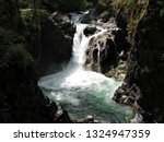 Little Qualicum River flowing downstream passing over bedrock edges creating waterfalls surrounded by rock cliffs and rock faces splashing into swim holes under bright sunshine