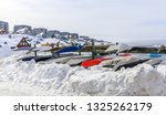 Inuit kayaks stored for a winter time in snow with Modern buildings and small cottages in the background, Nuuk old city harbor, Greenland8