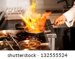 Chef cooking with flame in a frying pan on a kitchen stove. - stock photo