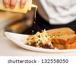 Chef pouring mayonnaise sauce on the vegetable salad with brown bread sandwich. - stock photo