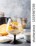 Small photo of Glass with Healthy homemade layered dessert trifle with orange, biscuit, yogurt and granola