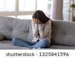 Small photo of Depressed young woman covering face by hands, crying alone at home, upset girl sitting on sofa, feeling unhappy after quarrel or breakup, despair and lonely, psychological problem concept