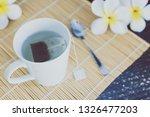 cup of dark tea on bamboo... | Shutterstock . vector #1326477203