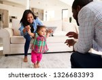 family at home encouraging baby ... | Shutterstock . vector #1326683393