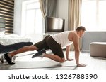 Stock photo young well built man go in for sports in apartment he stand on hands and move legs guy look 1326788390