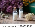 Small photo of Bottles of homeopathic globules with dried herbs and a materia medica, i.e. a book of remedies and their therapeutic properties, in the background
