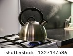 Small photo of kettle with boiling water. the kettle boils on a gas stove. the kettle whistles on the gas. steam from the kettle through the whistle.