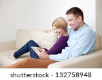 Happy young couple sitting on couch using digital tablet - stock photo