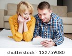 Happy couple lying on the floor with digital tablet - stock photo