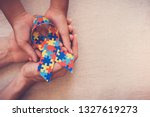 Stock photo hands holding puzzle ribbon for world autism awareness day pride jigsaw 1327619273