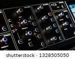 Small photo of Control panel with backlight buttons and knobs. Studio DJ mixer equipment for party and convert making. Modern digital equaliser, soundboard console. Sound recording and broadcasting technology