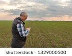senior farmer standing in wheat ... | Shutterstock . vector #1329000500