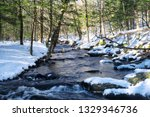 a snow covered stream flowing...   Shutterstock . vector #1329346736