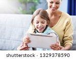 little girl and her mom using... | Shutterstock . vector #1329378590