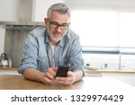 man texting casually in kitchen ... | Shutterstock . vector #1329974429