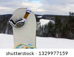 a snowboard stuck in the snow... | Shutterstock . vector #1329977159