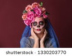 Small photo of Young woman with painted skull on her face for Mexico's Day of the Dead against color background