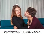 Small photo of Young woman pushing molesting rejecting man off when he wants to kiss her while sitting together on couch at home