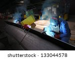 Two Welders Workers In The...