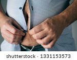closeup of a caucasian man, with a beer belly, trying to fasten the buttons of his shirt