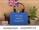 """Learning languages concept - blue paper with text """"Do you speak English?"""", flag of the Great Britain, headphones, books and chancellery on the table"""