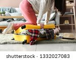woman trying to close suitcase... | Shutterstock . vector #1332027083