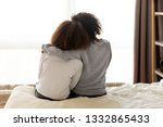Small photo of Rear back view black mother and daughter embrace sitting on bed at home, older sister consoling younger teen, girl suffers from unrequited love share secrets trustworthy person relative people concept