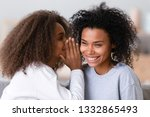 Small photo of Close up african mother best friend enjoy time gossiping with daughter, younger sister whispering secret in ear of confidant person, teenager girl chatting with nanny. Concept of trustworthy relations