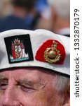 Small photo of Plymouth Devon November 2018. White beret worn by veteran solider with two regimental cap badges thereon in close up. One cloth and one gold coloured. View of eyes and nose only.