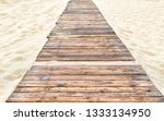 Panorama of deserted sandy beach with a wooden pathway in Anapa, Russia. Tourist track with an old decking to sea. Footpath is paved with vintage boards. Natural wood planks on the beach background.