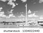 Small photo of Antigua, Antigua and Barbuda - December 13, 2016: modern yellow yacht or sailing boat or marine vessel under bare poles at moorage at pier in sea dock or bay on sunny day on blue sky