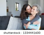 pretty woman kissing senior...   Shutterstock . vector #1334441600