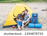 Stock photo people tourism and nature concept couple having fun on camping trip with cat 1334878733