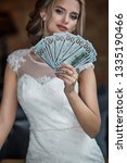 A Bride Holds Dollars Fan In...