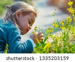 little boy enjoying flowers... | Shutterstock . vector #1335203159