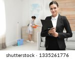 Small photo of Housekeeping manager checking maid work in hotel room
