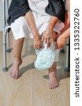 elderly woman changing diaper... | Shutterstock . vector #1335322760