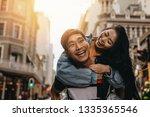 asian man giving piggyback ride ... | Shutterstock . vector #1335365546