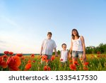 family in red poppy field | Shutterstock . vector #1335417530
