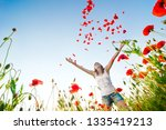 girl stands in poppy field | Shutterstock . vector #1335419213