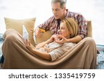 woman using laptop with husband ... | Shutterstock . vector #1335419759