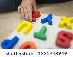 child's hand playing with abc... | Shutterstock . vector #1335448949