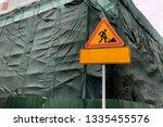 an orange sign warning of... | Shutterstock . vector #1335455576