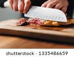 chef slicing ribeye steak on a...   Shutterstock . vector #1335486659