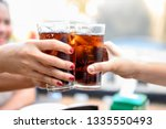 the woman's hand holds a glass... | Shutterstock . vector #1335550493