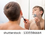 Teenage boy using a bathroom mirror to shave in the morning - stock photo
