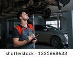 Evaluates damage. Man at the workshop in uniform using notepad for his job for fixing broken car. - stock photo