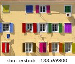 Small photo of Colorful windows with louvered shutters