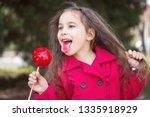 adorable little girl eating red ... | Shutterstock . vector #1335918929